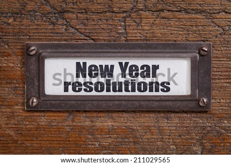 New Year resolutions  -  file cabinet label, bronze holder against grunge and scratched wood