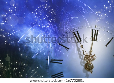 New Year's at midnight  - fireworks, and clock close to midnight - stock photo