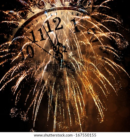New Year's at midnight - old clock and fireworks - stock photo