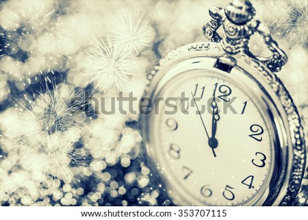 New Year's at midnight - Old clock with fireworks, snowflakes and holiday lights - stock photo