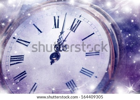 New Year's at midnight - Vintage photo of old clock with stars and snowflakes  - stock photo