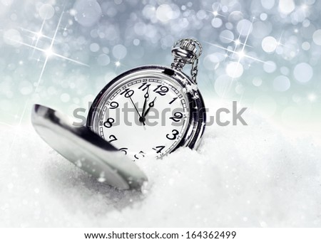 New Year's backgrounds .pocket watch in the snow - stock photo
