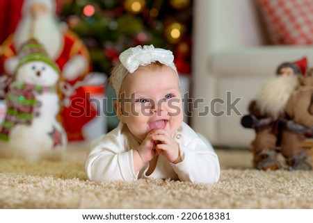 New Year's Concept. Adorable little girl near a Christmas tree with presents laughs. new year fun game - stock photo