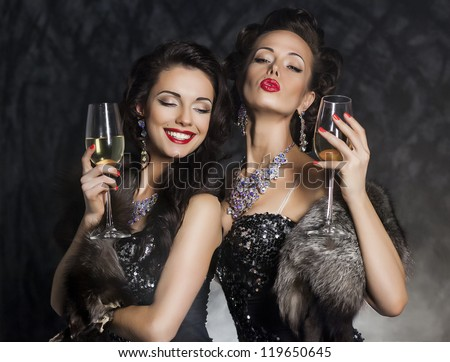 New Year's Eve of two beautiful young women with wine glasses - stock photo