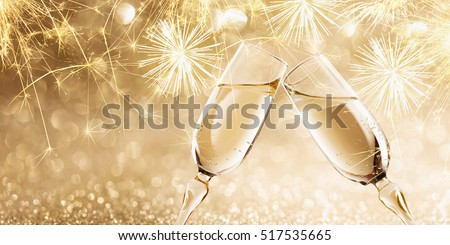 New Year's fireworks with glasses of champagne. Golden Holiday background