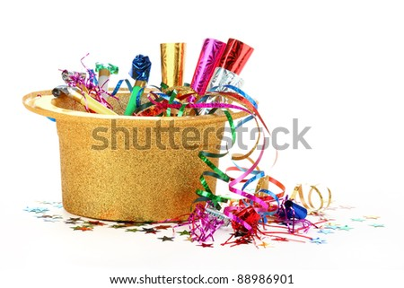 New Year's hat filled with noise makers, streamers and confetti on white background. - stock photo