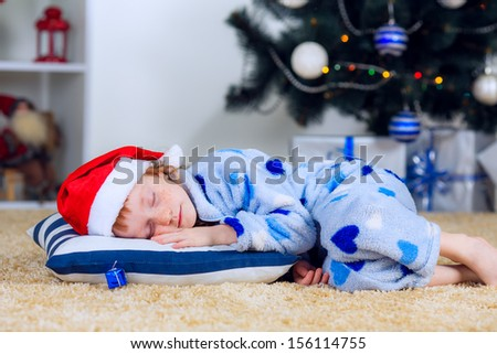 New Year's holidays. child fell asleep near the Christmas tree waiting for Santa Claus - stock photo