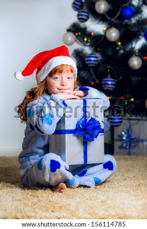 New Year's holidays. child with a gift near the Christmas tree - stock photo