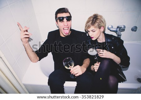 New Year's Party. Girl and boy sitting in the bathtub drinking and having fun  - stock photo