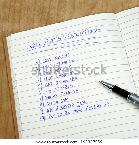 New Year's resolutions listed in the notepad  - stock photo