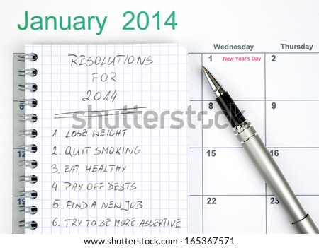 New Year's resolutions listed in the notepad with calendar and pen - stock photo