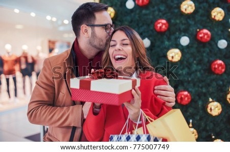New Year's surprise for a girlfriend. Beautiful young couple looking for Christmas and New Year's presents, having fun together in shopping mall. Consumerism, love, dating, lifestyle concept