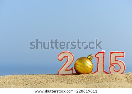 New year 2015 sign with christmas ball on a beach sand - stock photo
