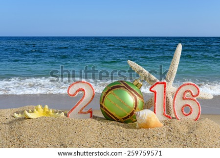 New year 2016 sign with seashells, starfish and christmas ball on a beach sand - stock photo