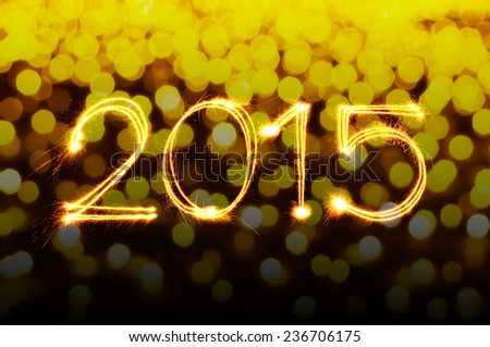 New year 2015 sparklers firework with unfocused yellow bokeh background - stock photo