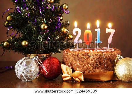 New Year 2017 still life. Chocolate cake and artificial fir tree with burning candles on brown background