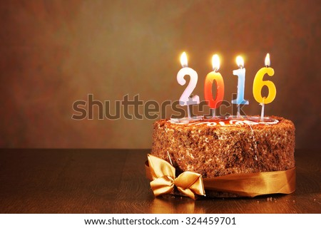 New Year 2016 still life. Chocolate cake and burning candles on brown background - stock photo