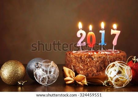 New Year 2017 still life. Chocolate cake and decorative tree balls with burning candles on brown background