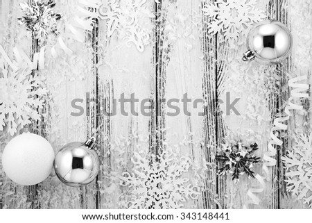 New year theme: Christmas tree white and silver decorations, balls, snow, snowflakes, serpentine on white retro stylized wood background black and white - stock photo