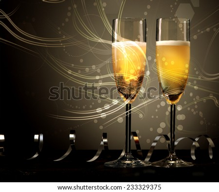 New Year, wedding or anniversary background of two elegant flutes of champagne with swirling light and twirled party streamers or ribbons with copyspace for your greeting on a dark background - stock photo