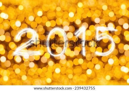 New Year 2015 writing sparkle firework figures on defocused gold light blur bokeh background - stock photo