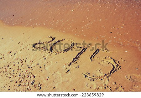new year 2015 written in sandy beach. image is retro filtered