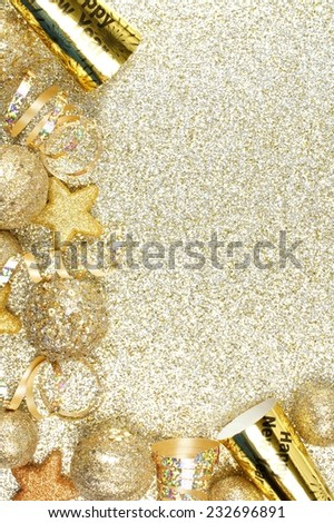 New Years Eve corner border of streamers and decorations over a glittery gold background - stock photo