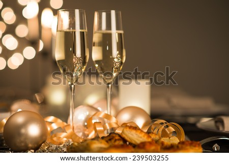 new years eve party table with two champagne flute ribbon and glitter  - stock photo