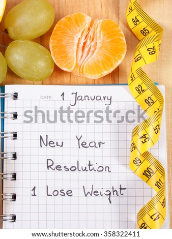 New years resolutions lose weight written in notebook and fresh fruits with tape measure, concept of healthy lifestyle - stock photo