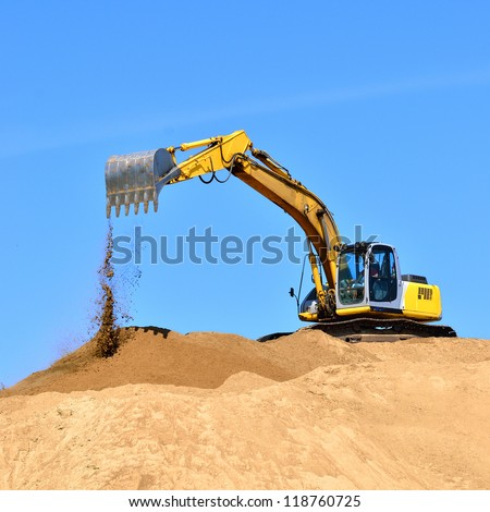 new yellow excavator working on sand dunes - stock photo