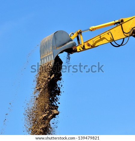 new yellow excavator working on sand dunes. Scoop close-up - stock photo