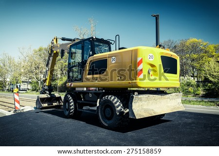 New yellow modern excavator building road in city. - stock photo