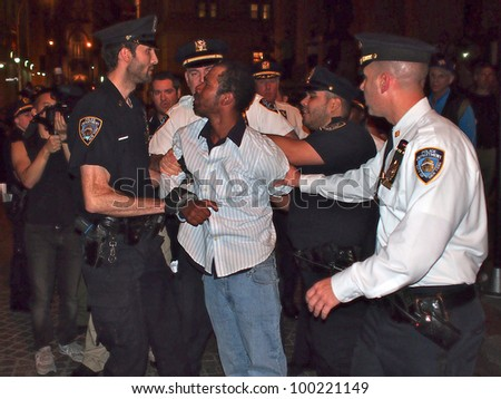 NEW YORK - APR 16: Police arrest an unidentified man at an Occupy Wall Street rally, April 16, 2012 in New York City. Demonstrators were holding a protest on the steps of Federal Hall. - stock photo