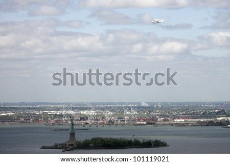 NEW YORK - APRIL 27: A NASA jet carries the Space Shuttle Enterprise over the Statue of Liberty on April 27, 2012 in New York City. The Enterprise will be on display at The Intrepid.