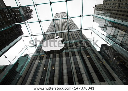 NEW YORK APRIL 5: the Apple Store with big logo surround by skyscrapers in Fifth Avenue in New York on 5 april 2012. the store is designed as the exterior glass box above the underground display room - stock photo