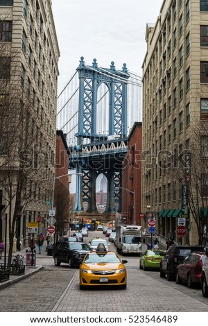 NEW YORK - APRIL 8: Yellow cab in Brooklyn cobble stone street with Manhattan Bridge in background on April 8, 2015. Brooklyn is located across East River