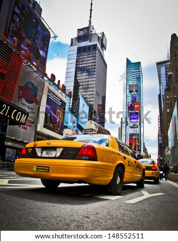 NEW YORK - APRIL 18: Yellow cab speeds through Times Square the busy tourist intersection of neon art and commerce and is an iconic street of New York City on April 18th, 2010 in New York, NY, USA.