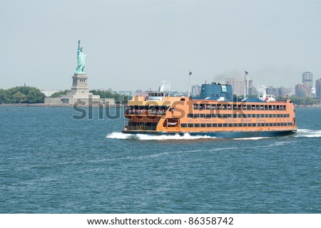 NEW YORK - AUG 03: Staten Island Ferry cruises past the Statue of Liberty on August 3, 2011 in New York.  The Ferry provides transportation to 20 million people a year and is free of charge. - stock photo