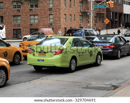 """NEW YORK - AUGUST 11: A special green """"Boro Taxi"""" cab on August 11, 2015 in New York. Boro taxis are allowed to pick up passengers in upper Manhattan and the outer boroughs of New York City. - stock photo"""