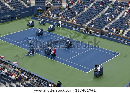 NEW YORK - AUGUST 27: Crew members clean the Ash Stadium court after the rain during 1st day of US Open Tennis Championship on August 27, 2012 in Flushing Meadows in New York City - stock photo