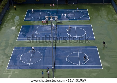 NEW YORK - AUGUST 27: Crew members clean the practice courts after the rain during 1st day of US Open Tennis Championship on August 27, 2012 in Flushing Meadows in New York City - stock photo