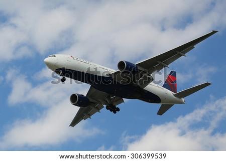 NEW YORK - AUGUST 13, 2015: Delta Airlines Boeing 777 descending for landing at JFK International Airport in New York - stock photo