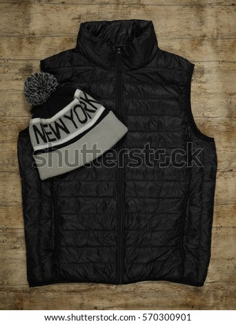New York Beanie and Black Gilet on a wood background