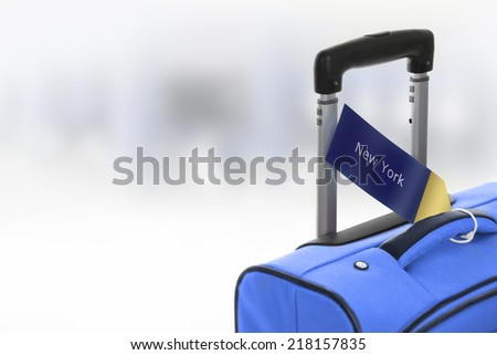New York. Blue suitcase with label at airport. - stock photo