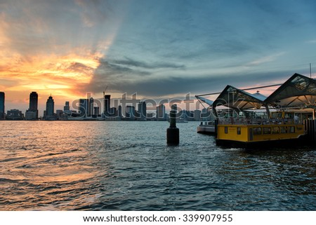 NEW YORK - CIRCA AUGUST 2015: Scenic View of Manhattan Skyline at Sunset with Heavy Dramatic Clouds as seen from Ferry Dock in New Jersey Across Hudson River. Circa August 2015 in New York, USA - stock photo
