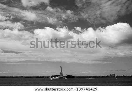 NEW YORK, CIRCA: Statue of Liberty under the cloudy sky in long distance view in New York in CIRCA. it represents the dreams of anyone from anywhere who wants to come to USA in search of a better life