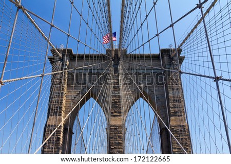New York City - American flag flying on the Brooklyn Bridge  - stock photo