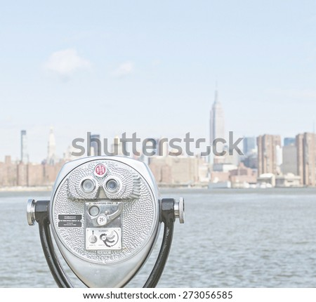 NEW YORK CITY - APRIL 21: Binoculars looking at New York City Manhattan skyline with Empire State Building over East River with vintage effect on April 21, 2015 in New York City.  - stock photo