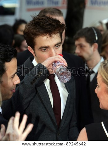 "NEW YORK CITY - APRIL 17: Robert Pattinson grabs a drink of Evian bottled water at the worldwide premiere of 20th Century Fox's ""Water For Elephants"" in New York City on April 17, 2011."