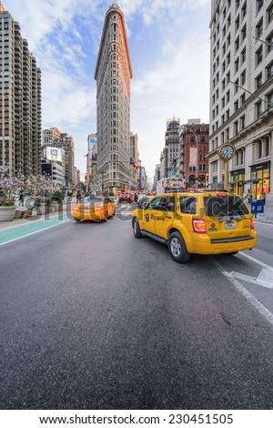 NEW YORK CITY - APRIL 15, 2014: Taxis stop under the Flatiron Building. Finished in 1902, the landmark skyscraper was designated a City Landmark in 1966 and a National Historic Landmark in 1989. - stock photo